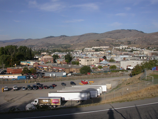 Photo of a view of the City of Vernon: a parking lot, buildings, and mountains in the background.